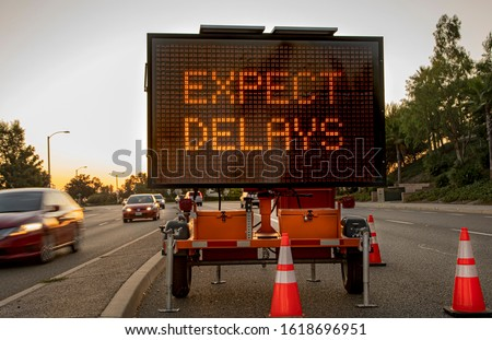 "Mobile Electronic Traffic Sign stating ""expect Delays"" taken at sunset with traffic blurred driving past the sign and traffic cones"