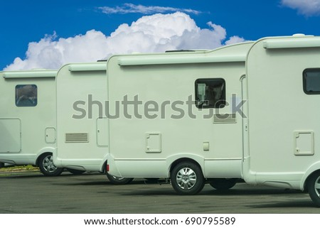 Mobile homes in a row in the background a blue sky. Concept freedom, family holiday travel, vacation travel with camper. #690795589