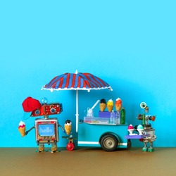 Mobile ice cream cart, miniature toy shop business. The robot seller holds ice cream waffle cones and the second robotic customer carries a tray with a dessert. Blue background, copy space.