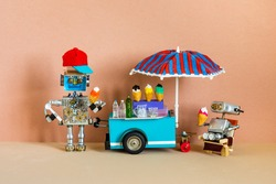 Mobile ice cream lemonade shop. Toy cart with a big umbrella, robot shopman holds waffle cone of ice cream. Metal robot is resting in a wooden deck chair. Sandy yellow beach background.
