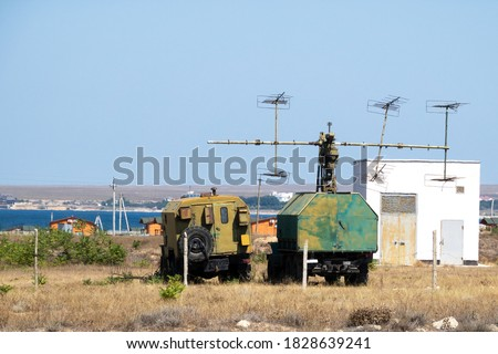 Photo of  Mobile military radar station on wheels for detecting aerodynamic and ballistic objects. The military facility is located in the steppe on the seashore.