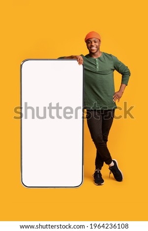 Mobile Offer. Happy Black Guy Leaning At Big Smartphone With Blank White Screen, Cheerful African Man Demonstrating Copy Space For Your Design Or Advertisement, Posing Over Yellow Background, Mockup