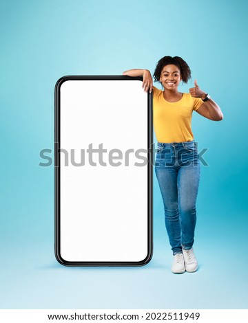 Mobile offer. Happy black lady leaning on huge cellphone with empty white screen, showing thumb up, recommending cool new app or website, offering space for your ad, mockup