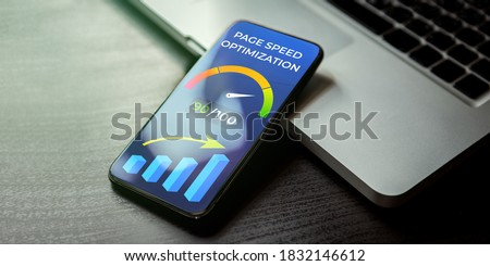 Mobile Page Speed Optimization concept. Website Page Speed Loading Time image for internet SEO. Mobile phone lying on a wooden table next to the laptop and on the screen accelerometer with high values