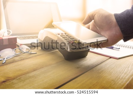 Mobile payments concept with EDC machine or credit card terminal with computer laptop and glasses. Warm toning effect.