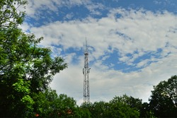 Mobile phone antenna on sky background with clouds