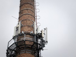 Mobile phone base station, on an old industrial brick chimney equiped with 3G, 4G and 5G antenna, at the top of a European building, used for cellular phone network coverage, reception & transmission