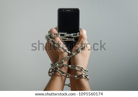Mobile phone chained to the hands of a man, telephone dependence