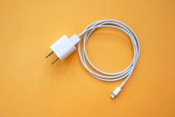Mobile Phone Charger on Orange Background Top View