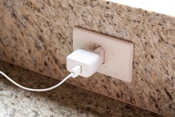Mobile phone charger plugged on wall outlet