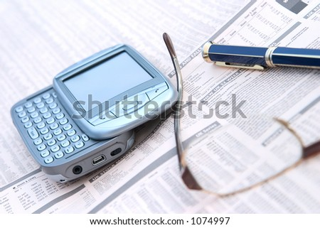 mobile phone, glasses, and a pen on top of a financial newspaper. Shallow Depth Of Field.