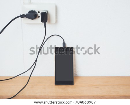 Mobile phone in charging plugged on white wall,low battery and charge concept. #704068987