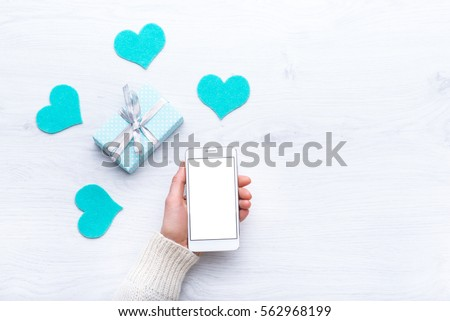 Mobile phone in hand. Portable communication device. Mobile applications. Online promotions and discounts. Holiday gifts and surprises. Present. Valentine's Day. Internet technologies #562968199