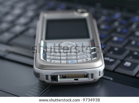 mobile phone lying on a laptop keyboard