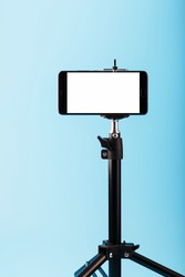 Mobile phone on a tripod with a clear white display for image and text, blue isolated background.