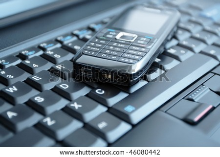 Mobile phone on laptop keyboard - business concept