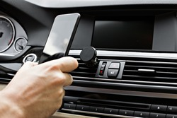 Mobile phone on magnet car mount phone holder for GPS. Lifestyles photo in car. Front view. With hand, phone.