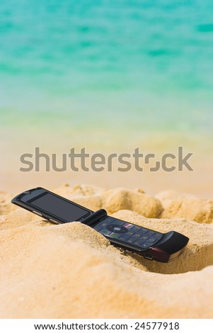 Mobile phone on sand beach, communication concept