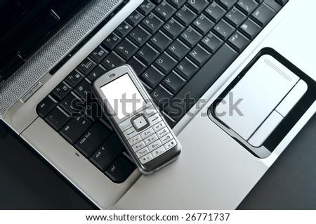 mobile phone over laptop keyboard closeup