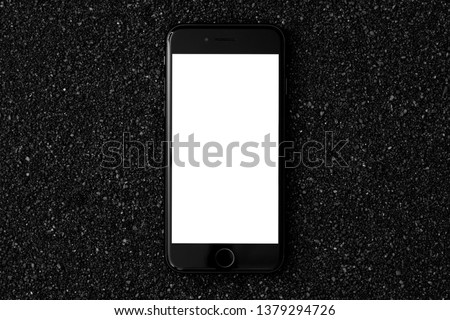 mobile phone smart phone flat lay on a black sand with white empty screen
