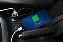 Mobile phone ,smartphone, cellphone is charged ,charge battery with usb charger in the inside of car. modern black car interior.