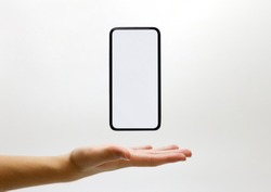 Mobile phone smartphone floating in palm of hand with a blank copy space display screen