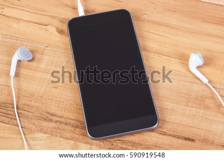 Mobile phone, smartphone with headphones on wooden board