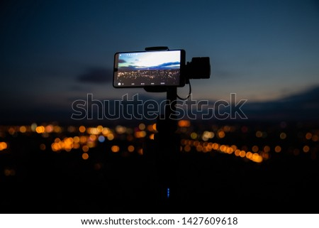 Mobile phone taking pictures on colorful sunset on Bila Hora with amazing view on city Brno Czech Republic pink and orange colors with many clouds and city lights