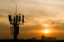 Mobile phone Telecommunication Radio antenna Tower with sunset sky, silhouette