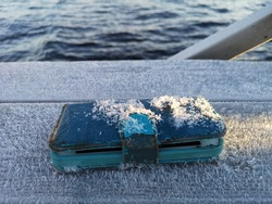 Mobile phone with a frosty wallet case by on the dock by the water