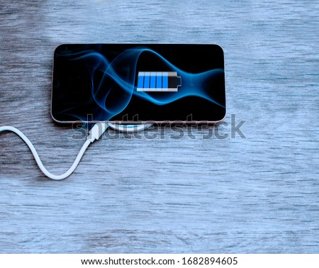 Mobile Phone with black screen and battery charging process on 5G network plugged in to Mobile Phone wireless Recharging.Smart phone connect with wireless rounded device for recharge.Copy space