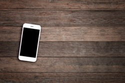 Mobile phone with blank screen on wooden table background. Smartphone on wood old plank vintage texture background. top view, copy space