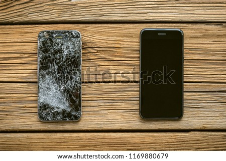 mobile phone with broken touchscreen on wooden background. #1169880679