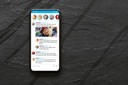 Mobile phone with sample social media microblogging app on the screen