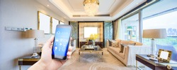 mobile phone with smart home app in modern living room