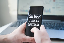 Mobile phone with text: silver futures contract and money, dollars in hand. Financial trading. Investment in precious metals. Playing on stock exchange, market manipulation.Losses, crisis.Short float.