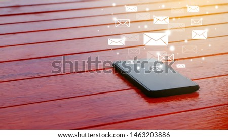 Mobile phones, smart phones with media icons and text symbols On a red wood table background.