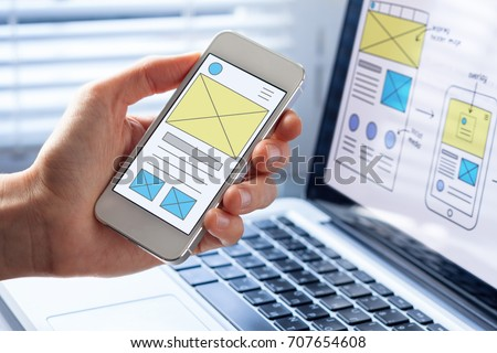 Mobile responsive website development with UI/UX front end designer previewing wireframe sketch layout design mockup on smartphone screen