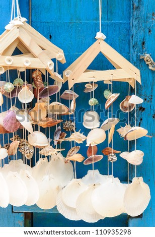 Mobile sea shell hanging on the blue door.