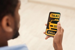 Mobile Service. Over the shoulder view of unrecognizable african american guy using modern application, ordering a taxi, holding smartphone, calling a cab, black and yellow screen app interface