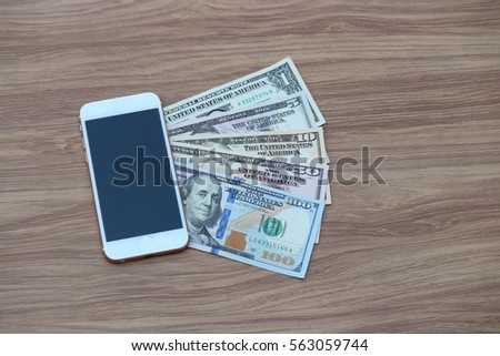 Mobile Smart phone and dollar cash on wood background, digital money and fintech concept
