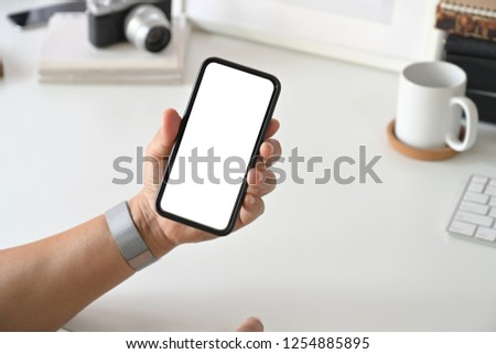 Mobile smart phone in man's hand at desk work. #1254885895