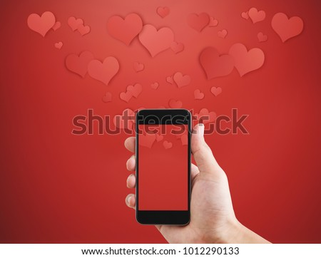 Mobile smart phone, on red background with floating hearts. Valentines, love message and texting concept #1012290133