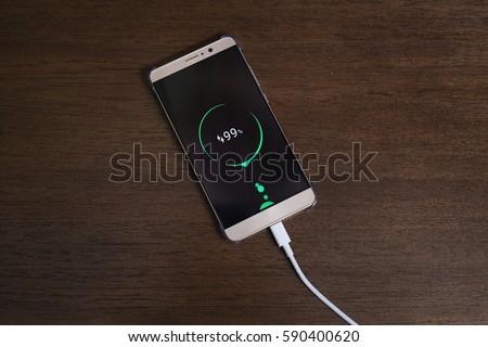 Mobile smart phones charging on wooden desk #590400620