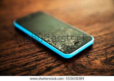 Mobile smartphone with broken screen on wooden background.