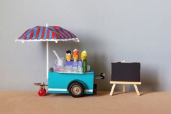 Mobile trolley ice cream lemonade shop. Ice cream in waffle cones, cold drinks. Big blue red umbrella and mockup advertising black chalk board on a wooden easel