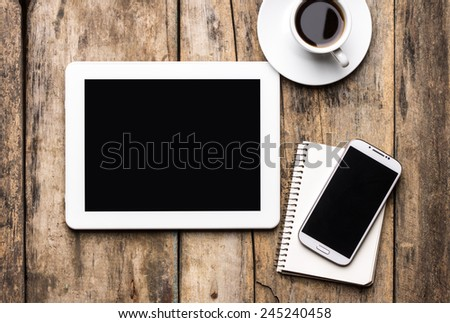 Mobile workplace with tablet PC, phone and cup of coffee on rustic wooden table. Top view image