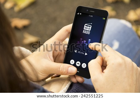 mobility and modern lifestyle concept: young woman listening radio app on the smartphone at the park