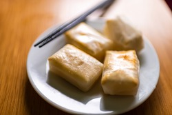 Mochi rice cakes roasted toasted baked in oven in traditional Japanese way on plate with chopsticks