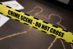 Mock crime scene with crime scene - Do Not Cross yellow ribbon and chalk body outline. Do Not Cross Crime Scene Police Tape, Bright Yellow with a Bold Black Print for High Visibility. Caution Danger